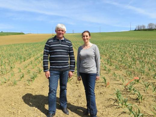 Alain and Céline pose in front of a field of young garlic