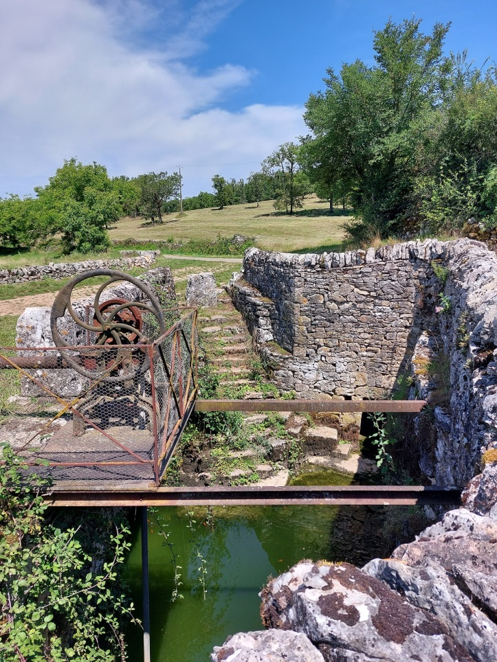 Pond surrounded by stone walls with old metal pump, SW France